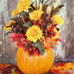 Fall centerpiece made with pumpkin, flowers, and leaves